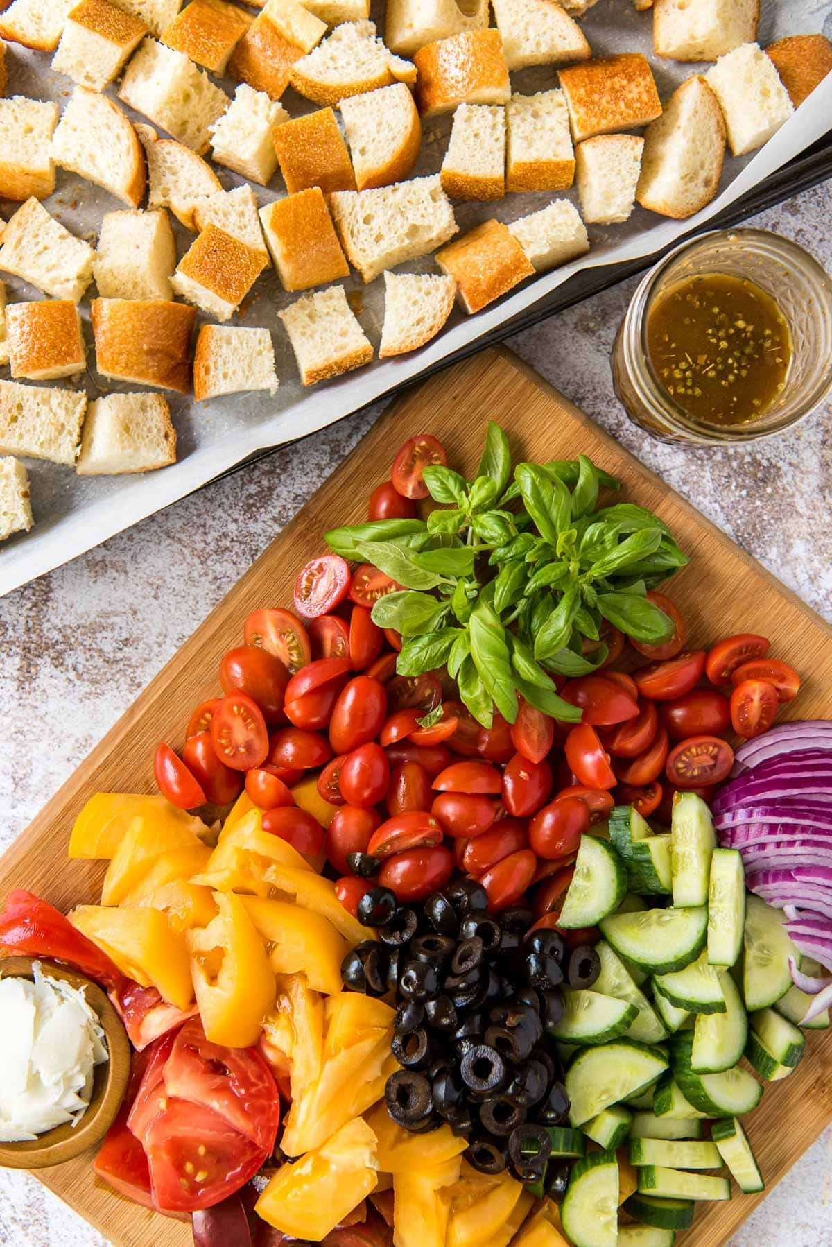 wood cutting board with tomatoes, peppers, olives, cucumbers, basil and bread