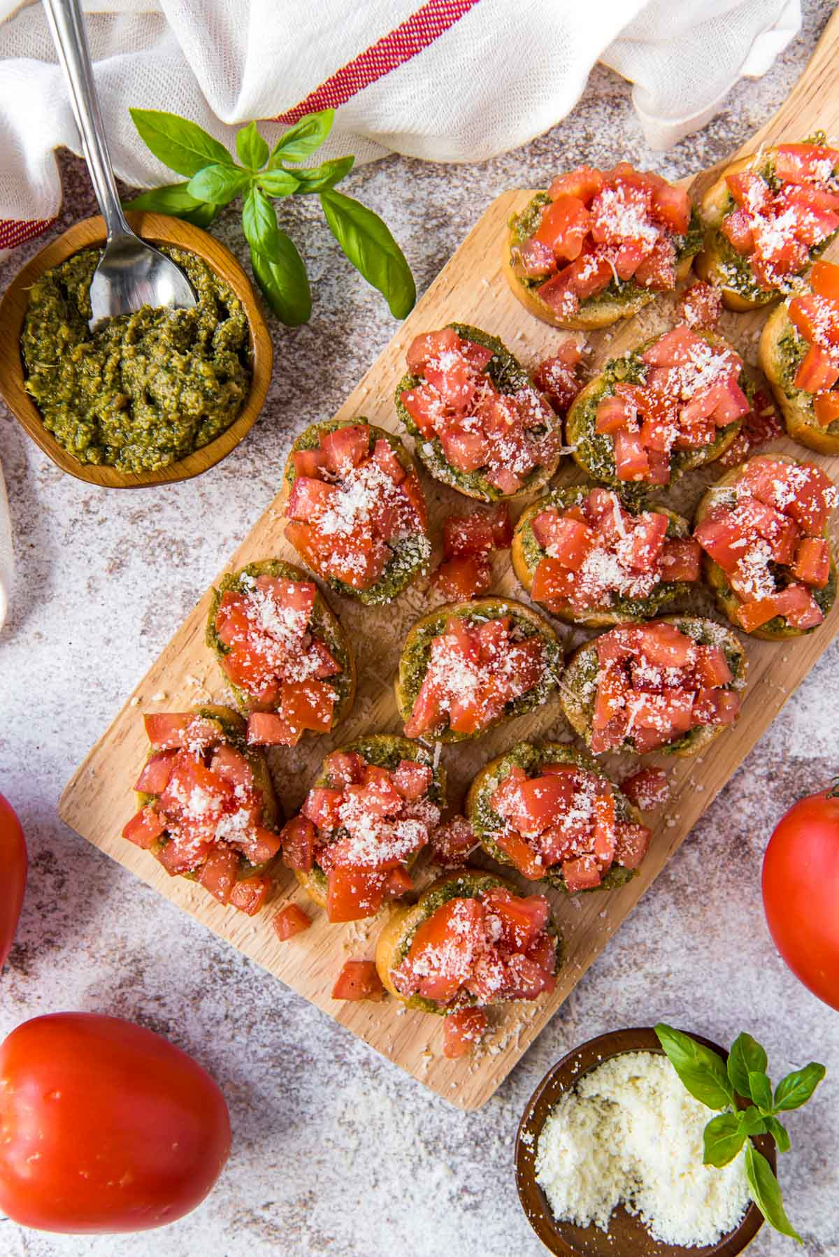wood cutting board with bruschetta pieces, a dish of pesto, a dish of parmesan cheese, tomatoes