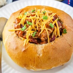 Bread bowl full of chili with a sprinkle of cheese and green onions.