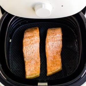 Two pieces of cooked salmon in an air fryer tray