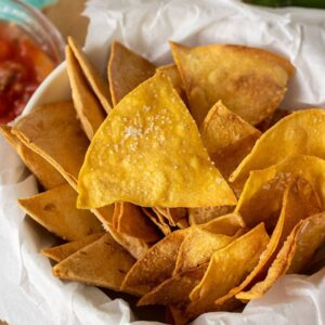 A dish filled with homemade tortilla chips sprinkled with salt.