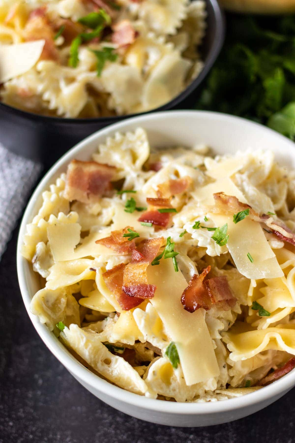 white bowl of pasta topped with bacon & parsley