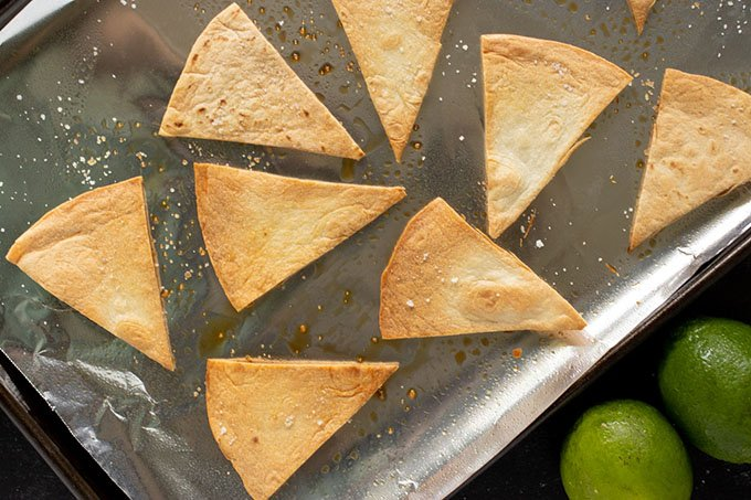 homemade tortilla chips on baking sheet with foil, two limes