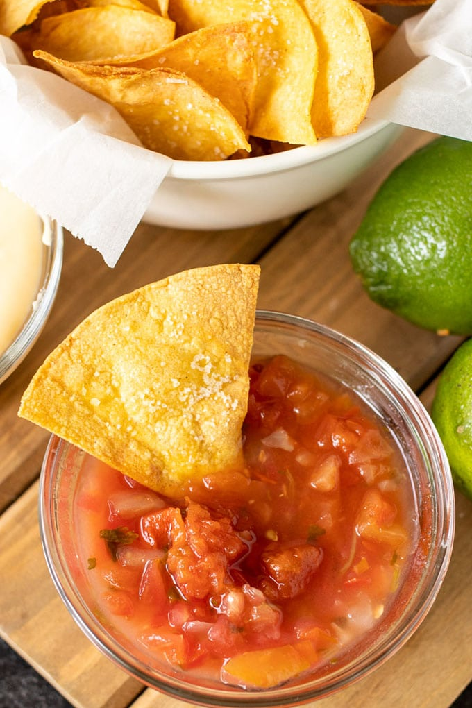 a white bowl lined with white paper and filled with tortilla chips, a clear dish of salsa with a tortilla chip in int, 2 limes
