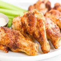 crispy chicken wings, celery and ranch on a white plate