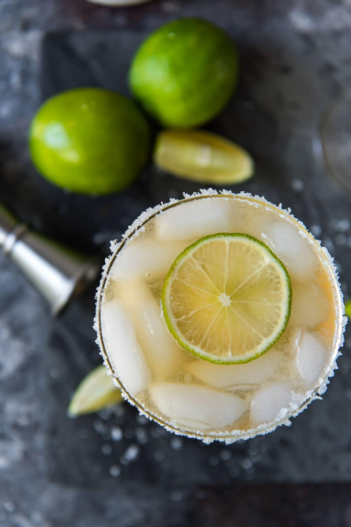 overhead shot of glass of margarita with jigger and limes below on a black background