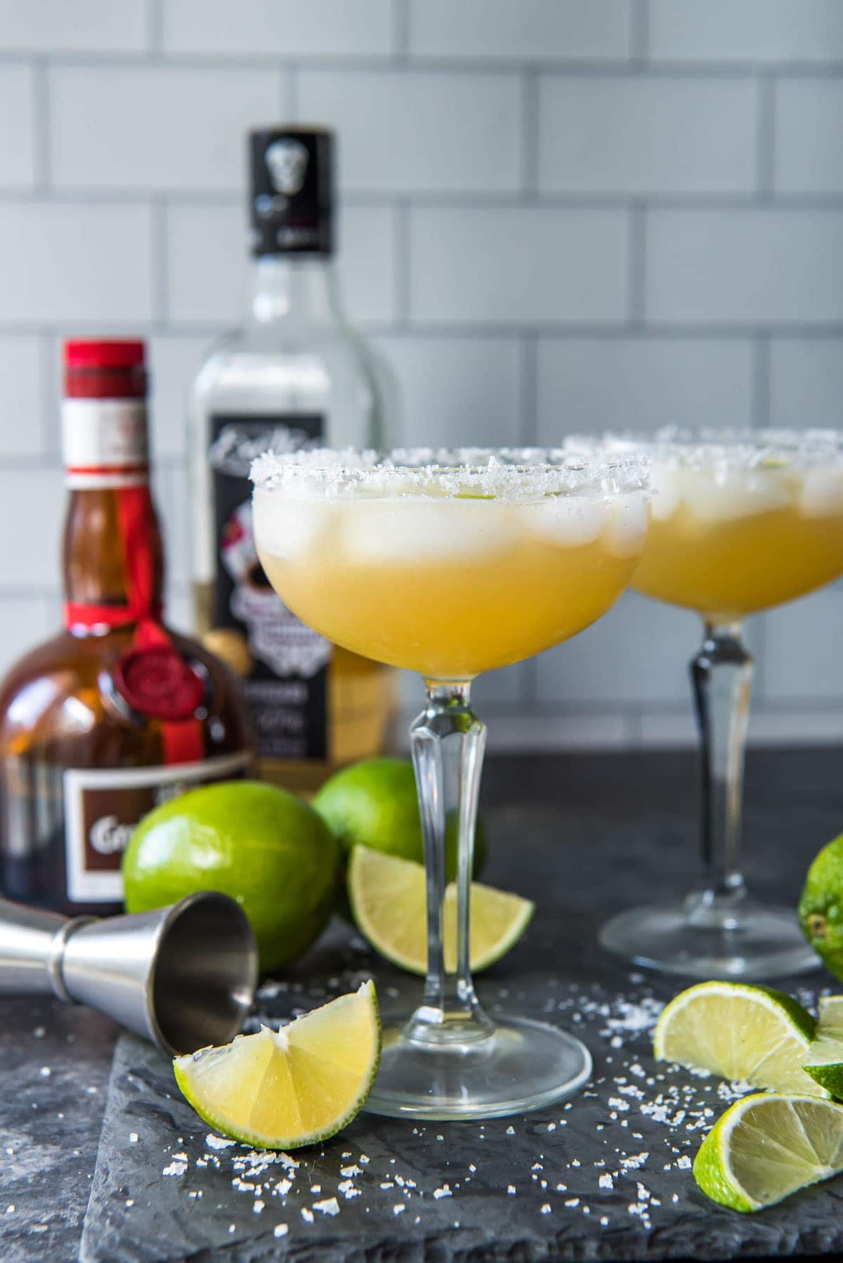 black background, lime wedges, glasses filled with cadillac margaritas, tequila, grand marnier bottles
