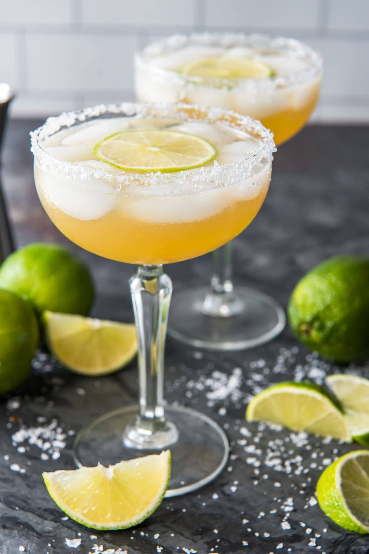 cadillac margarita filled glasses with lime wedges and coarse salt