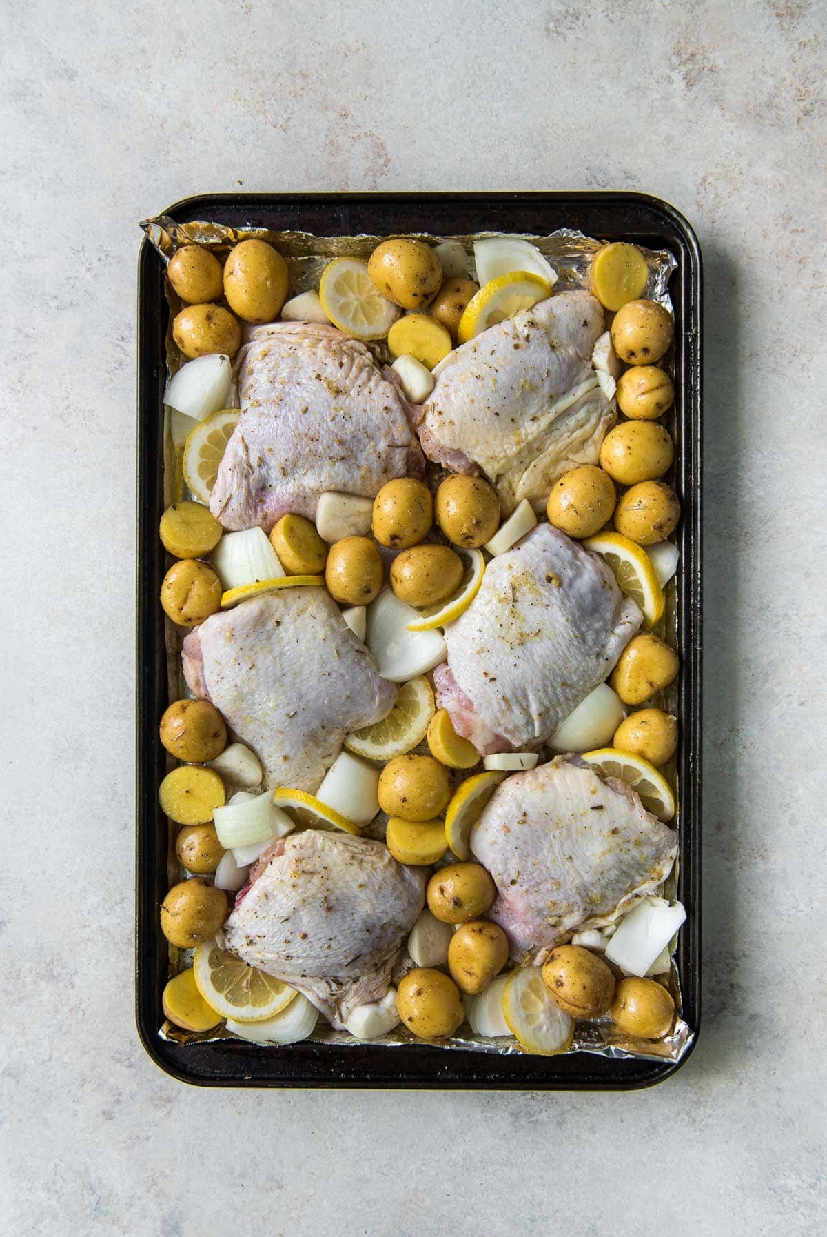 raw chicken thighs with skin, potatoes, onions and lemon slices