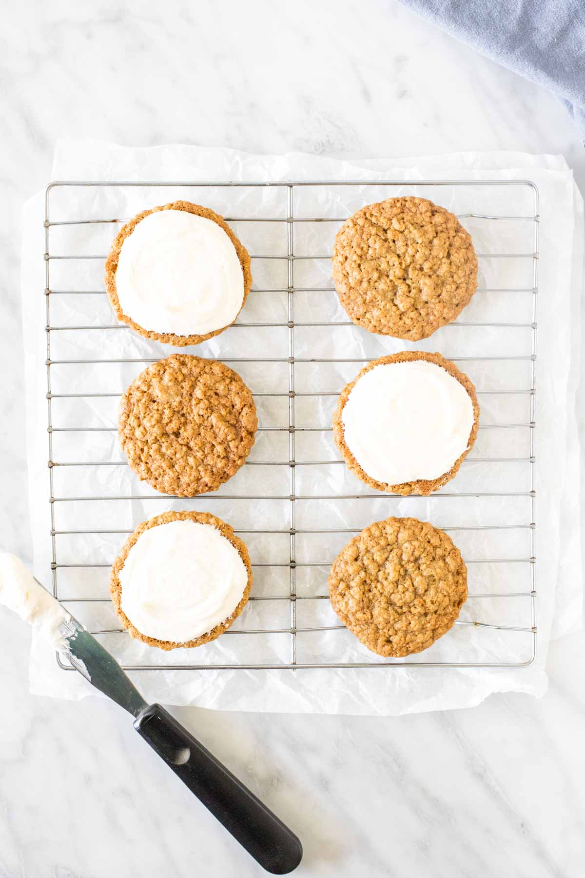 Oatmeal cookies with frosting on a wire rack.