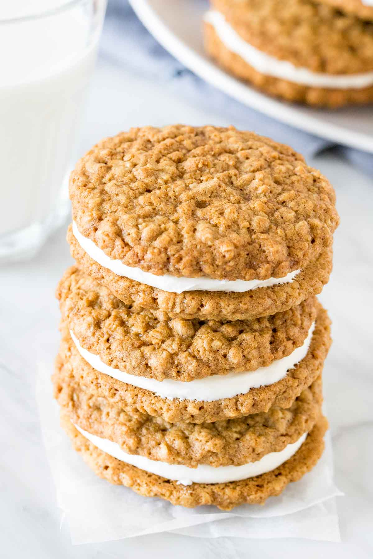 Stack of 3 oatmeal sandwich cookies with a glass of milk.