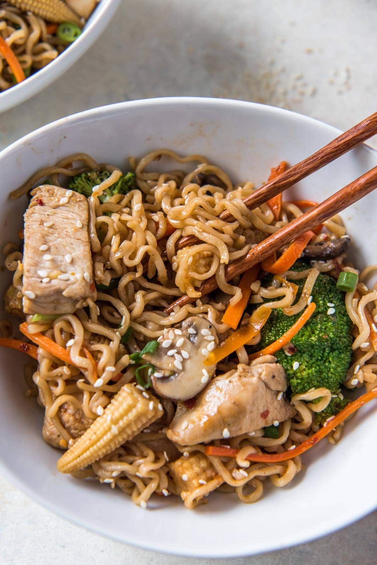 ramen noodles, chicken and vegetables in a white bowl with chopsticks