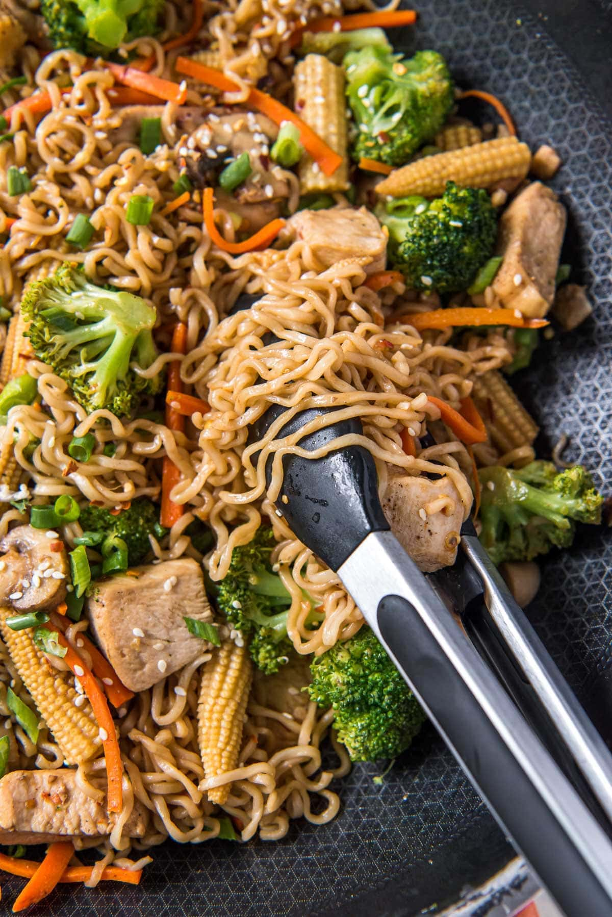 skillet with ramen noodles, stir fry with chicken and vegetables, black and silver metal tongs