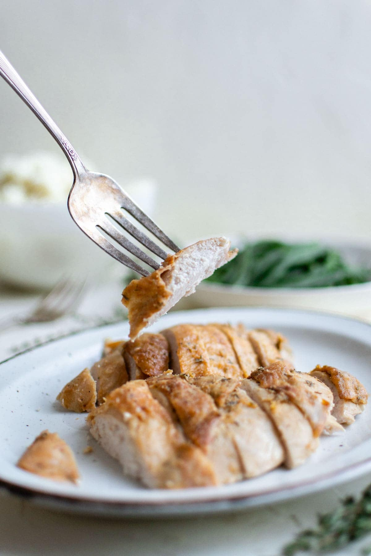 white plate with sliced turkey breast, a fork