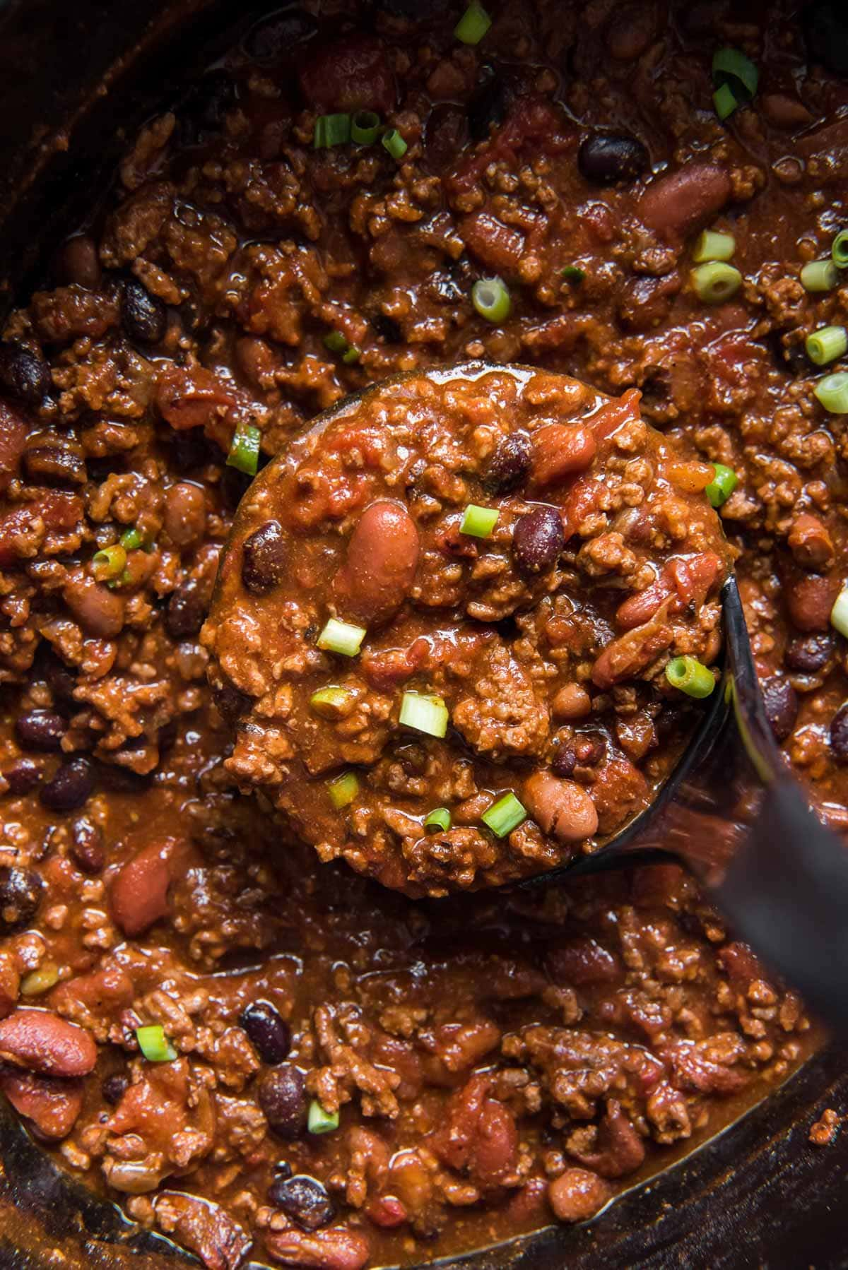 beef chili in a slow cooker pot, ladle
