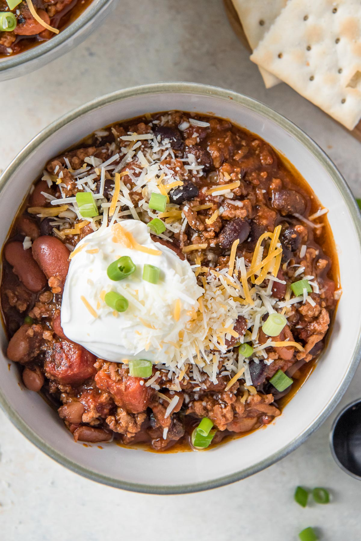 close up bowl of chili with sour cream and cheese