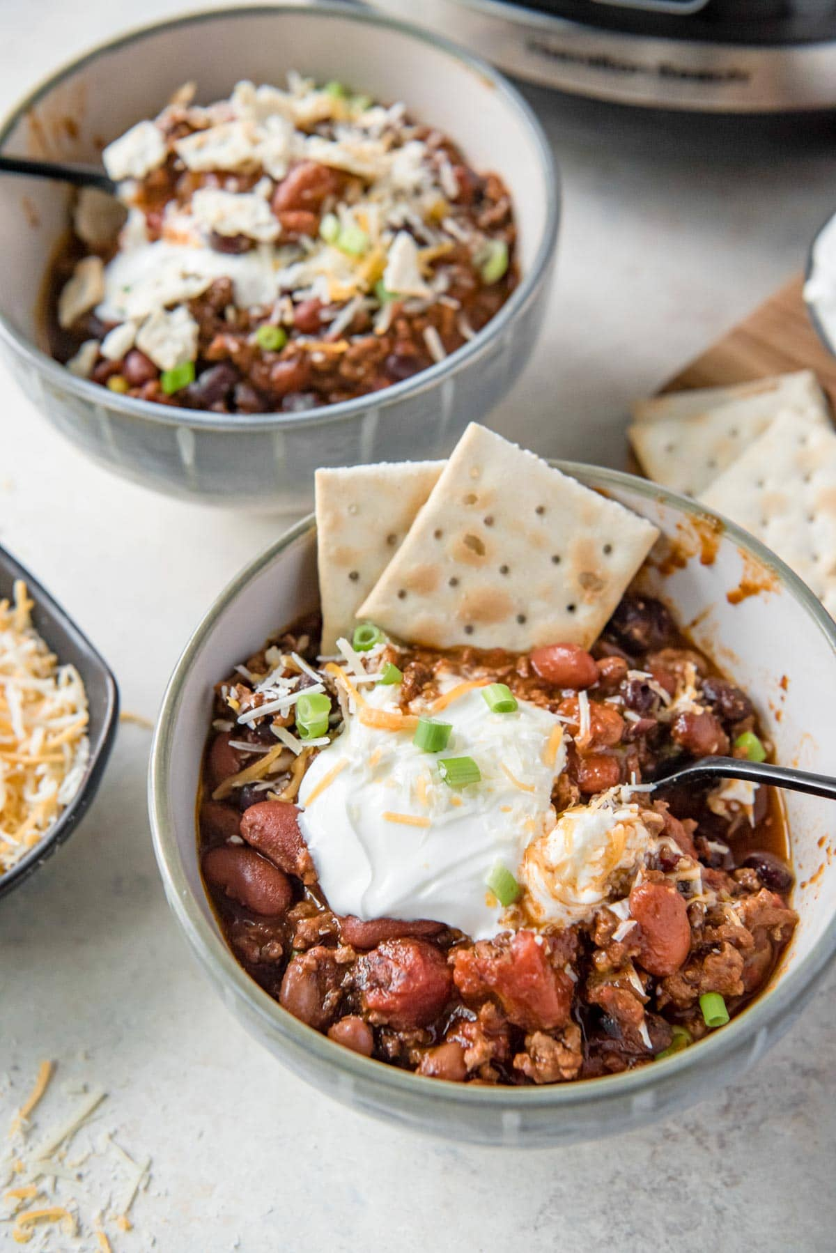 bowls with chili, sour cream, cheese, and crackers, spoon, slow cooker