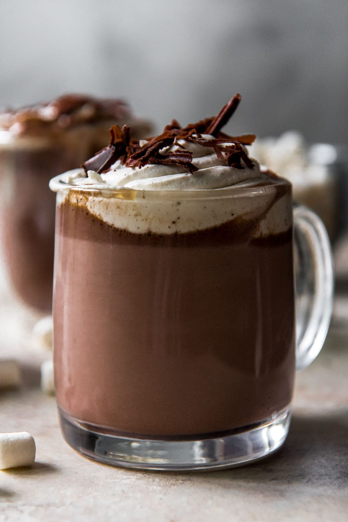 hot chocolate in clear glasses, whipped cream, chocolate shavings, marshmallows