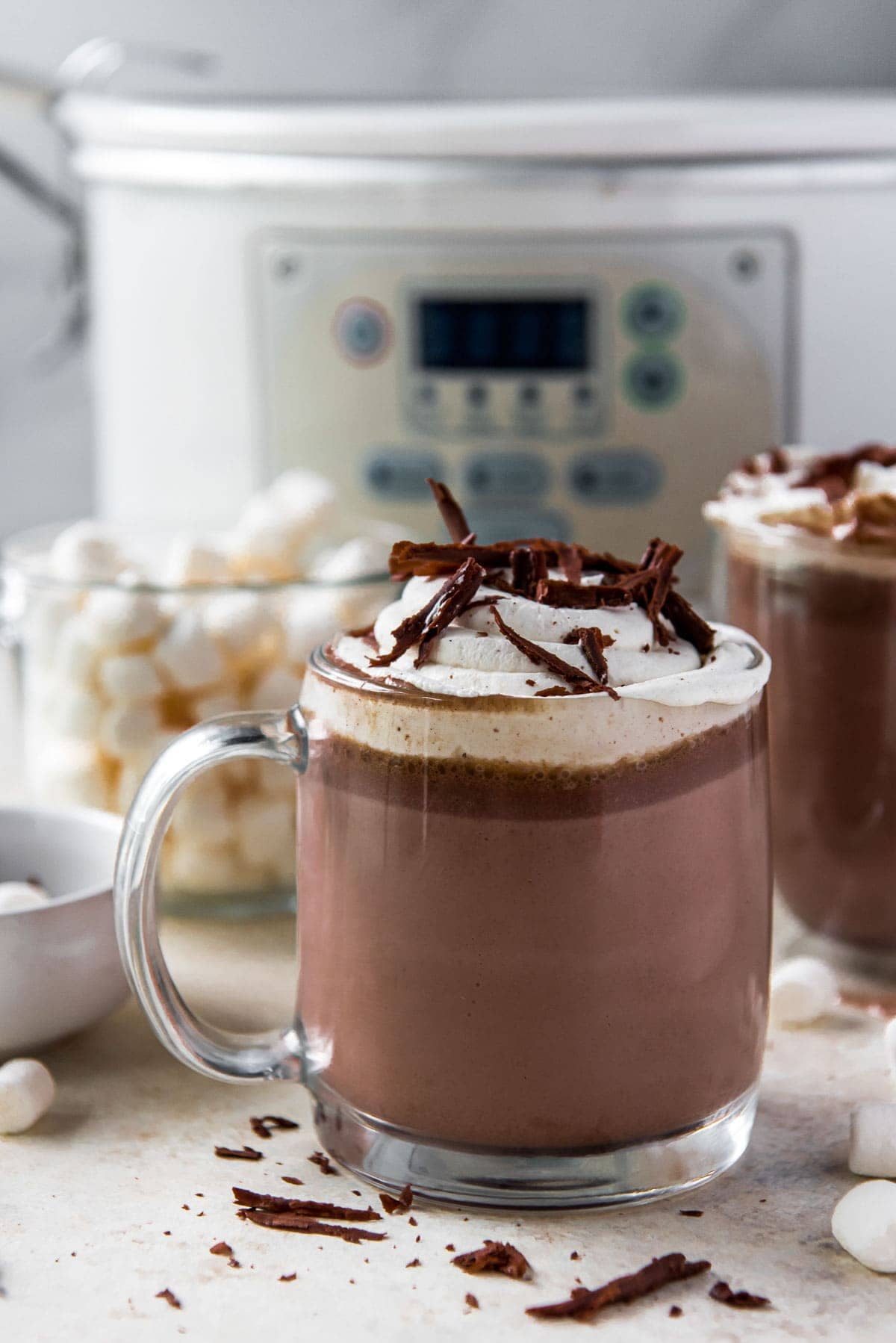 white slow cooker, hot chocolate in a clear glass, whipped cream, chocolate shavings, marshmallows