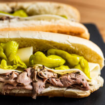 Italian beef sandwich on black slate board.