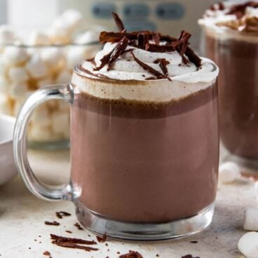 hot chocolate in a clear glass, whipped cream, chocolate shavings, marshmallows