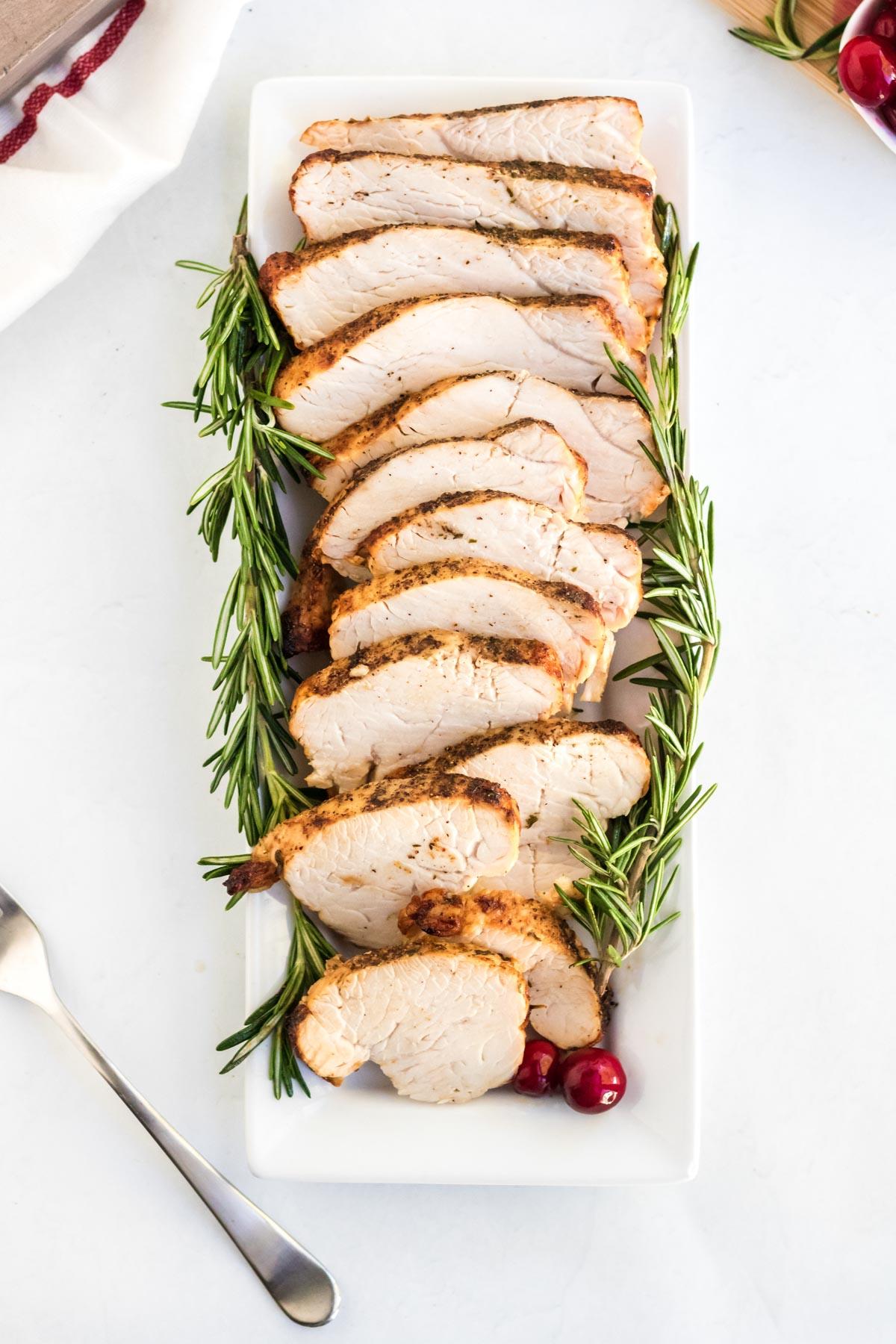 sliced turkey breast, fork, white platter