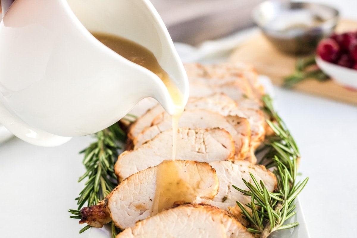 gravy boat, gravy, sliced turkey breast, cranberry