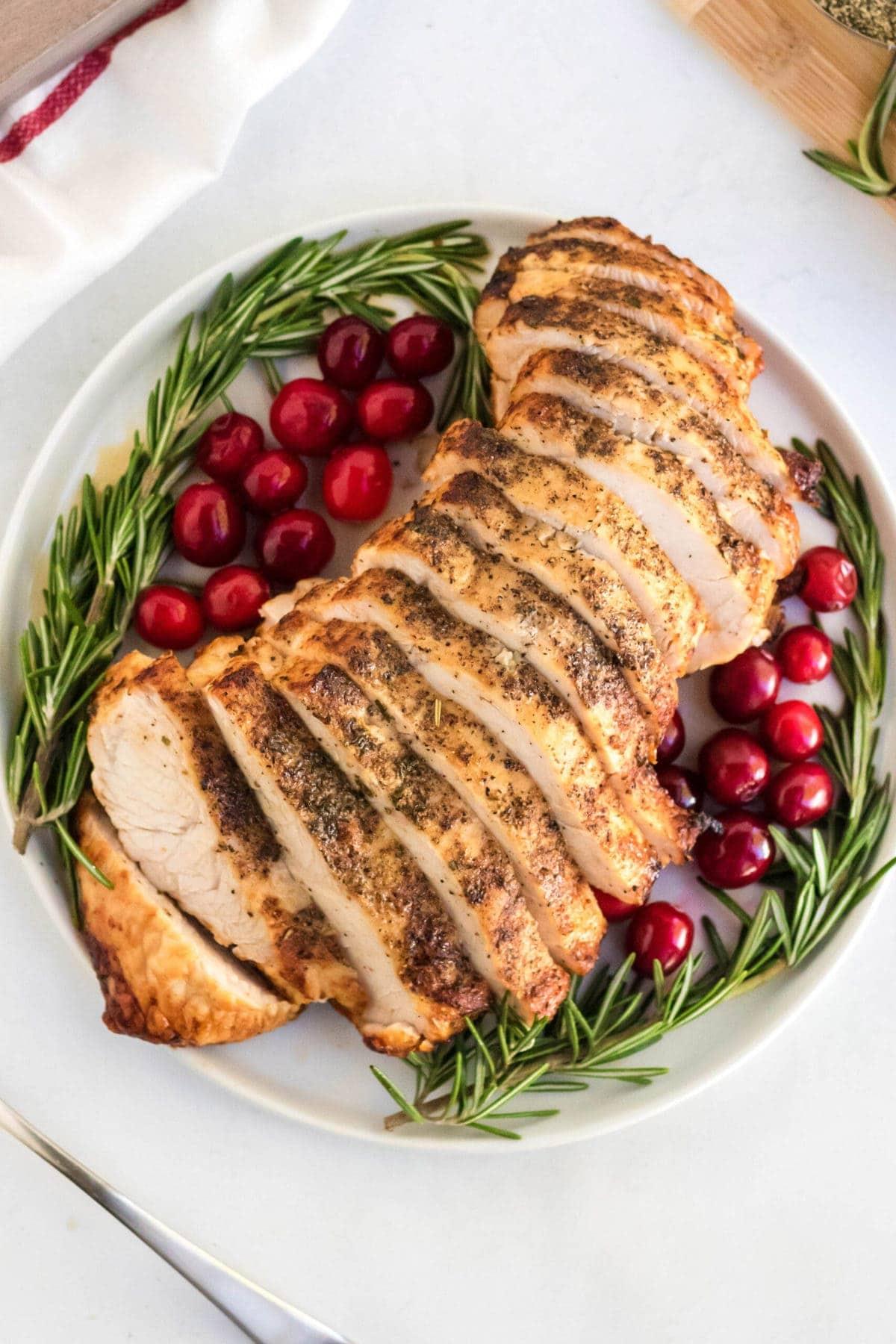 white platter, rosemary, cranberries, sliced turkey breast, fork