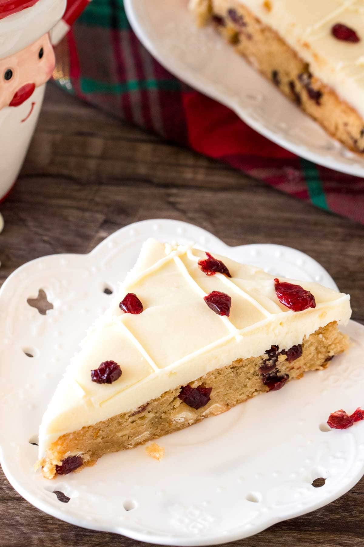 Slice of homemade cranberry bliss bar on a plate.