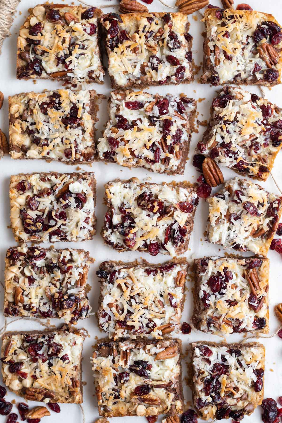 squares of cranberry magic bars on white background