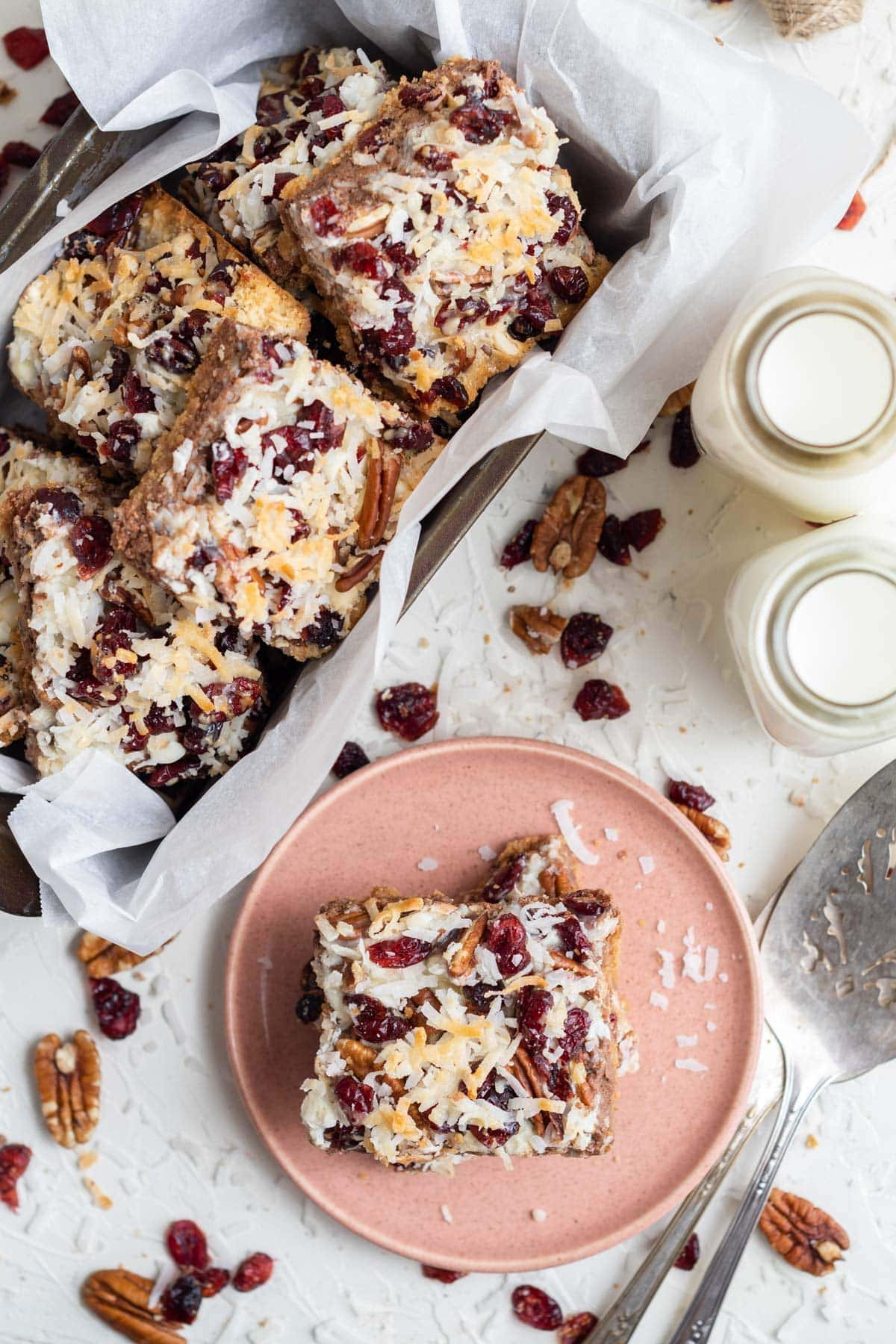 magic bars in a pan, one on a pink plate, 2 jars of milk, scattered chocolate chips, a silver serving spoon