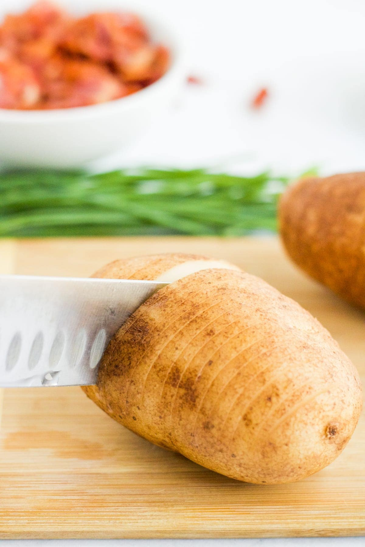 A russet potato being sliced to make Hasselback Potatoes