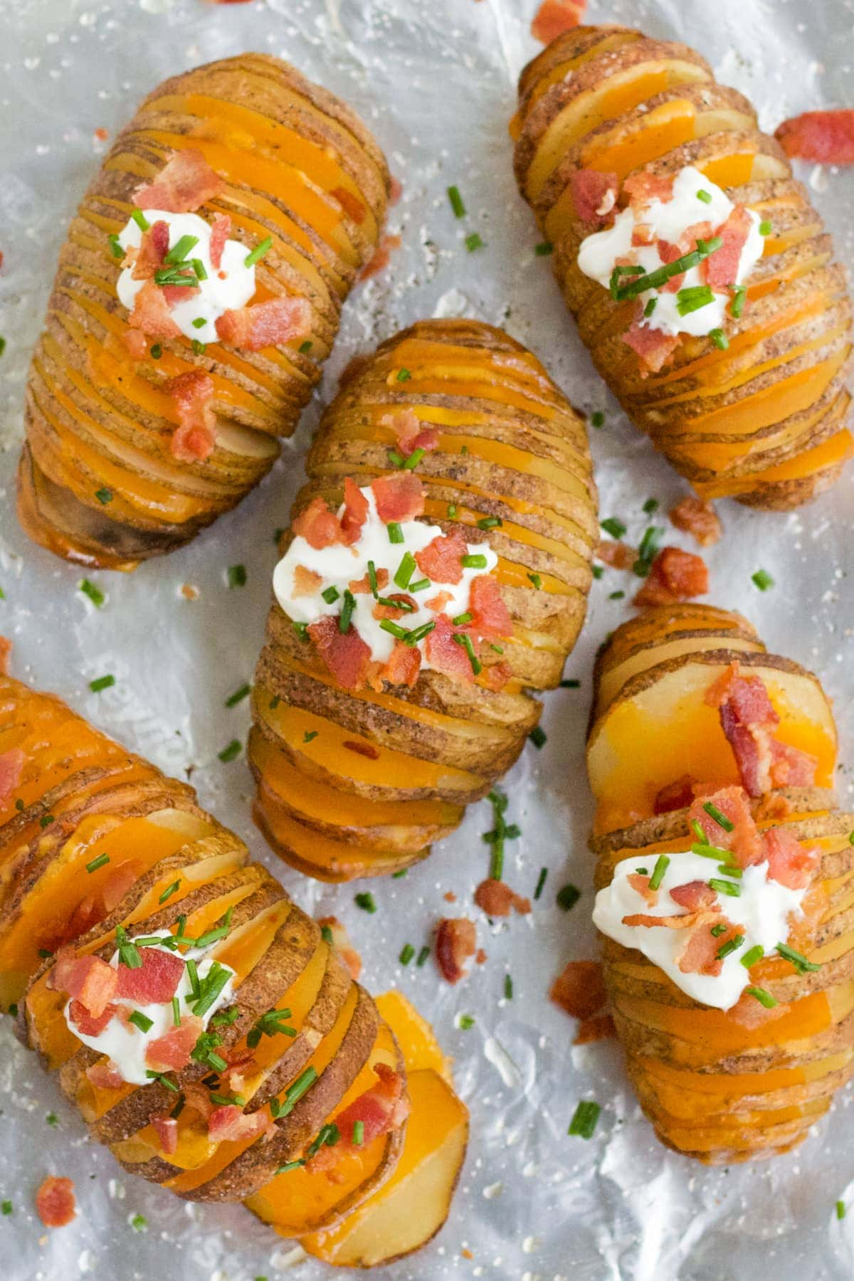 Hasselback Potatoes on a baking sheet with sour cream, bacon, cheddar cheese and chives.