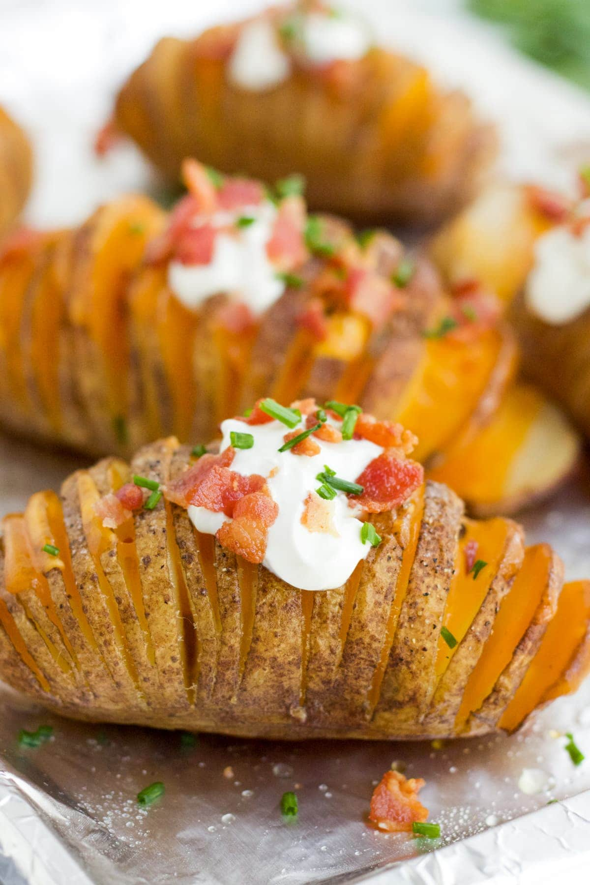 Hasselback potatoes on a baking sheet with fully loaded toppings