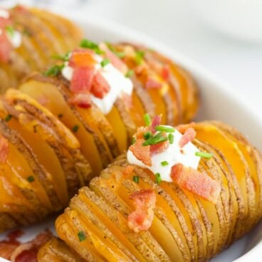 Hasselback Potatoes in a white serving dish with sour cream, bacon and fresh chives on top.