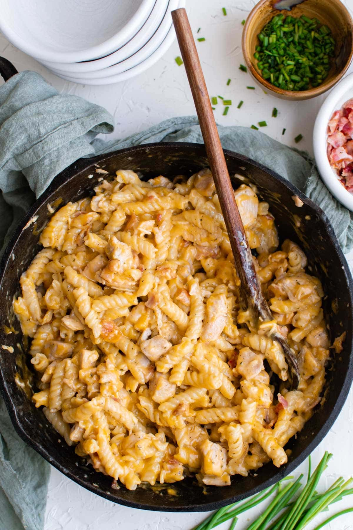cast iron skillet with cheesy pasta with chicken and bacon, bowl of bacon, bowl of chives, empty white bowls, wooden spoon