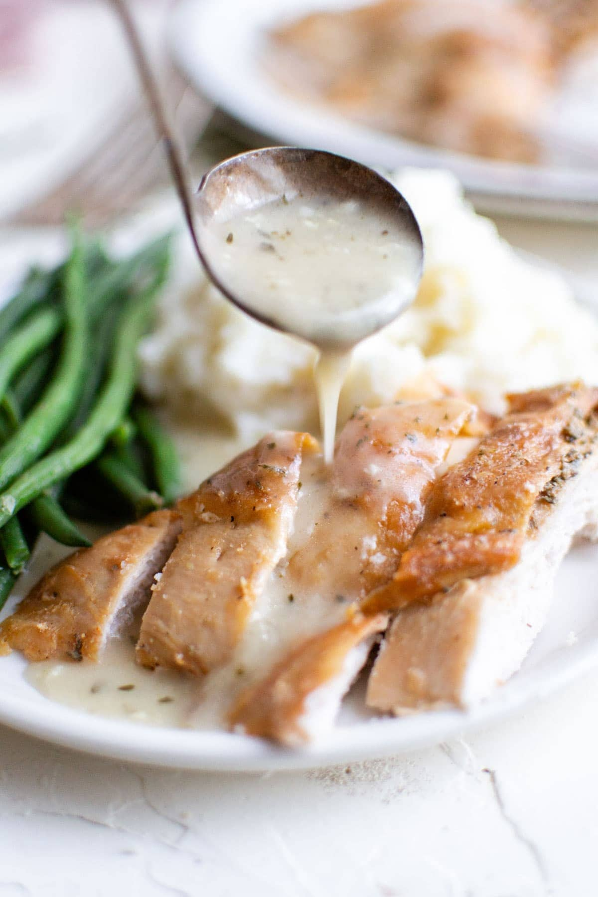 white plate, turkey sliced, green beans, mashed potatoes, spoon with gravy