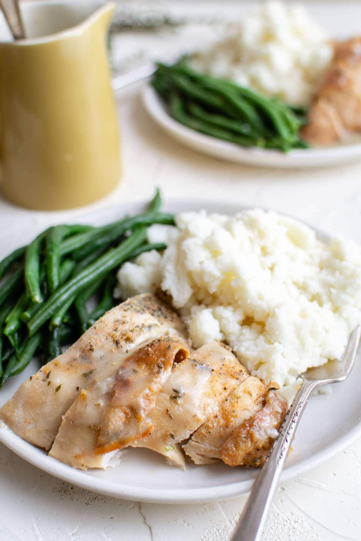 white plates with green beans, turkey, mashed potatoes and gravy