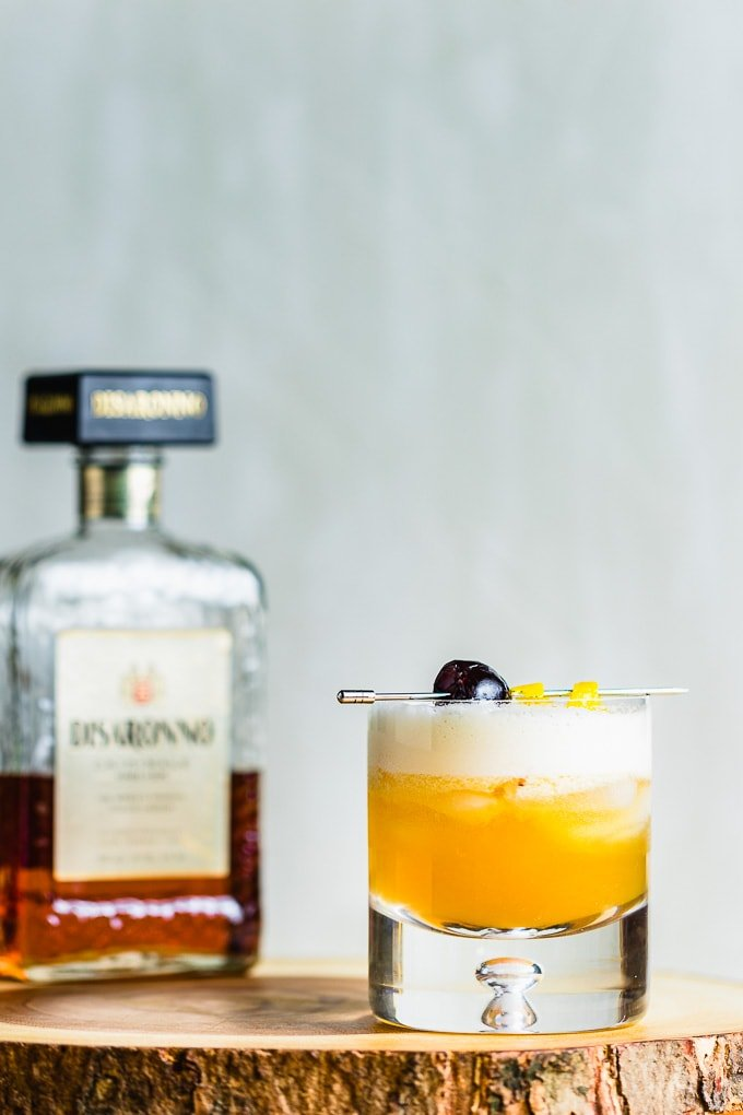 Rocks glass with amaretto sour garnished with cherry and lemon twist and a bottle of Amaretto.