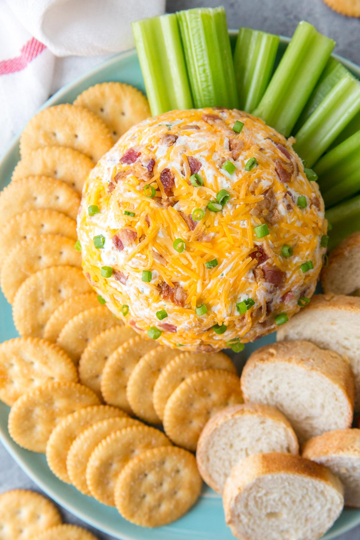 blue plate, crackers, slices of bread, celery, cheeseball with cheese, bacon and green onions