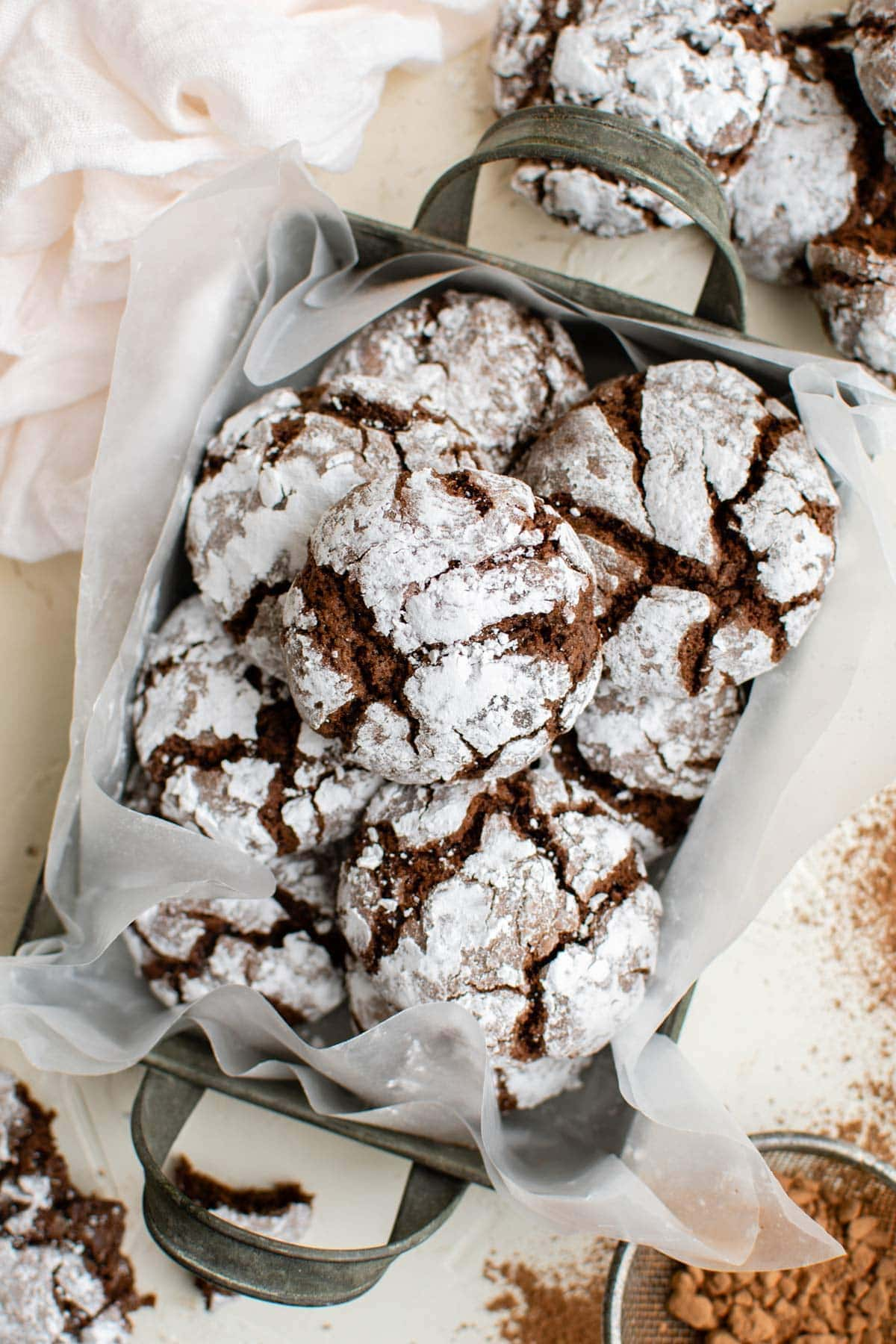 overhead shot of chocolate crinkle cookies in a box with parchment paper
