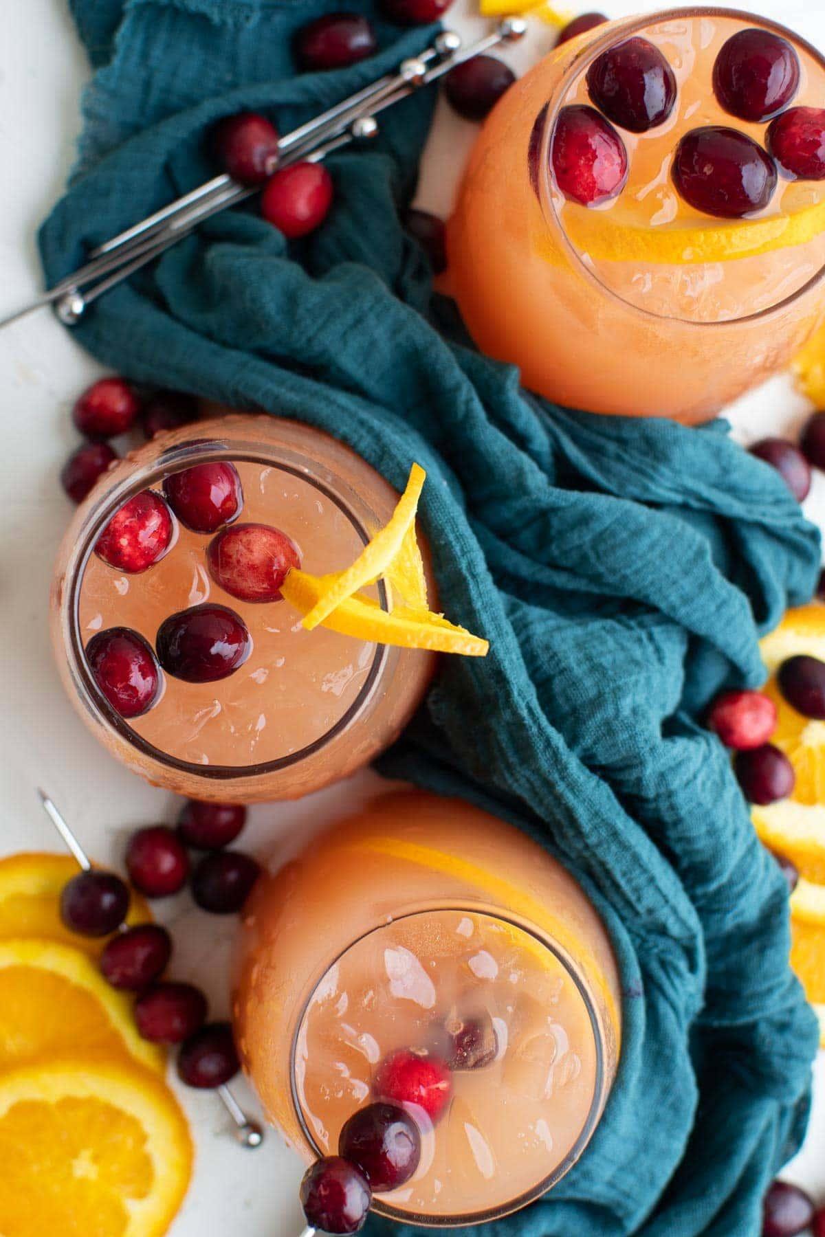 glasses of christmas punch, cranberries, orange slices, blue napkin