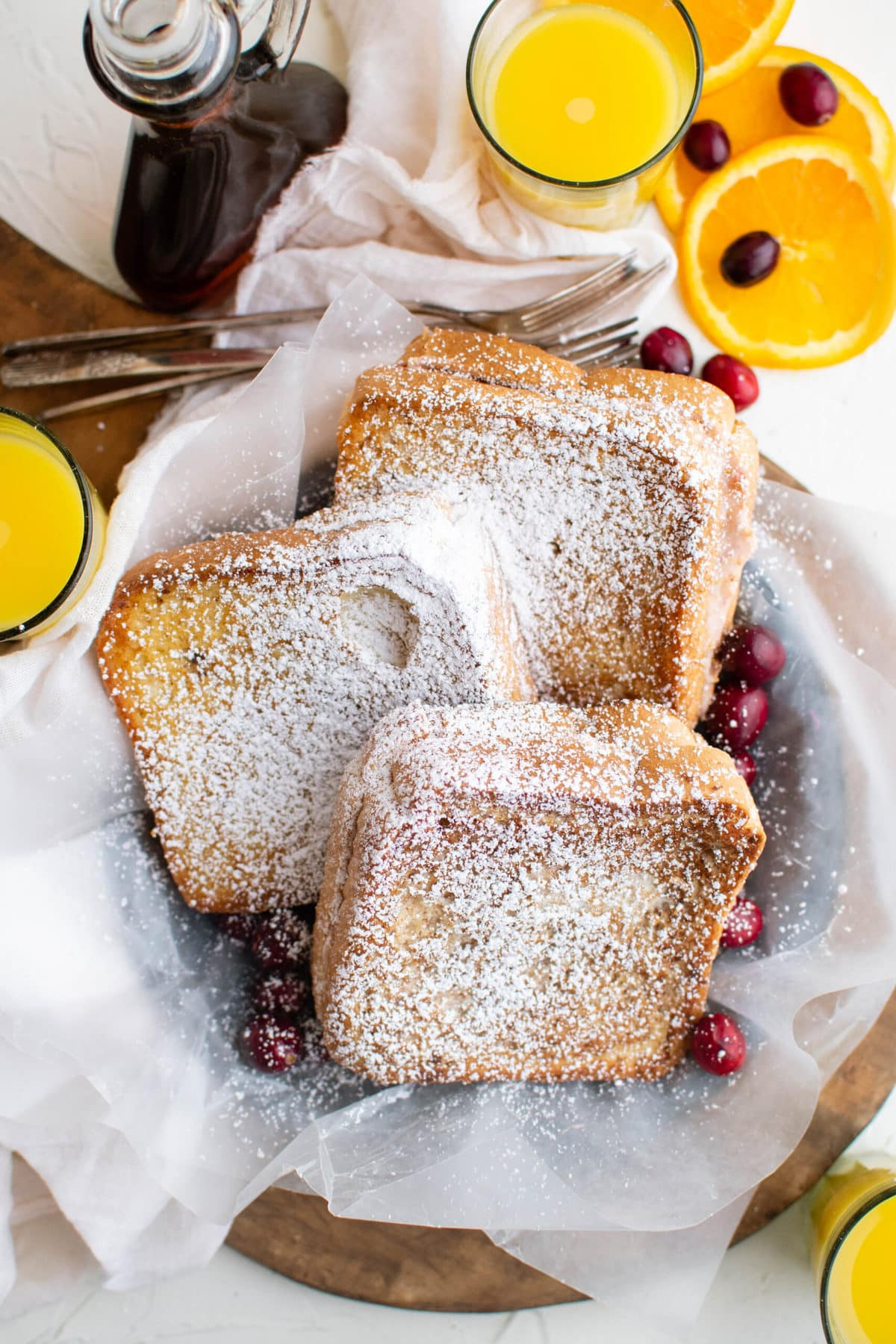 white napkin, powdered sugar covere french toast sandwiches, cranberries, orange slices, orange juice