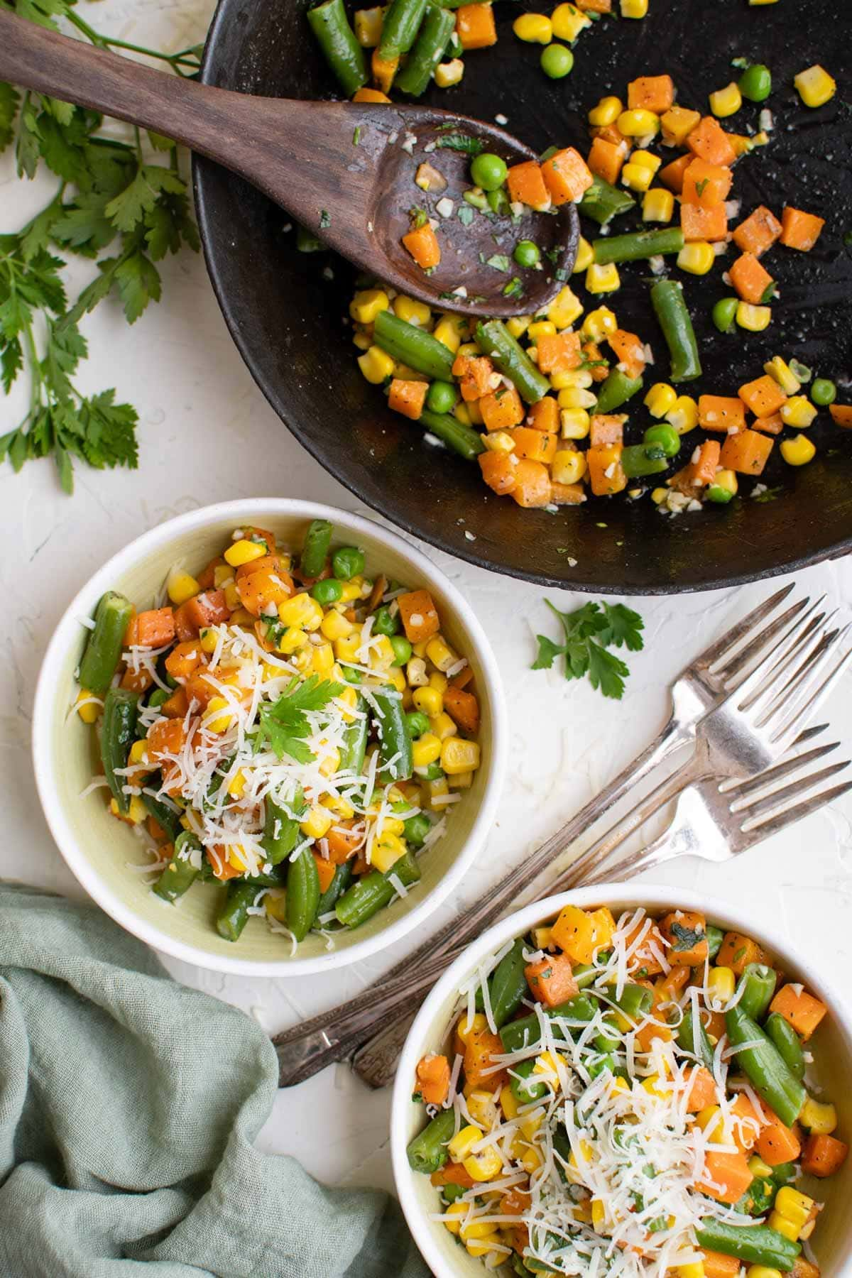skillet with garlic butter vegetables, two white plates with veggies and parmesan cheese, wooden spoon, parsley sprigs, 3 forks, green napkin
