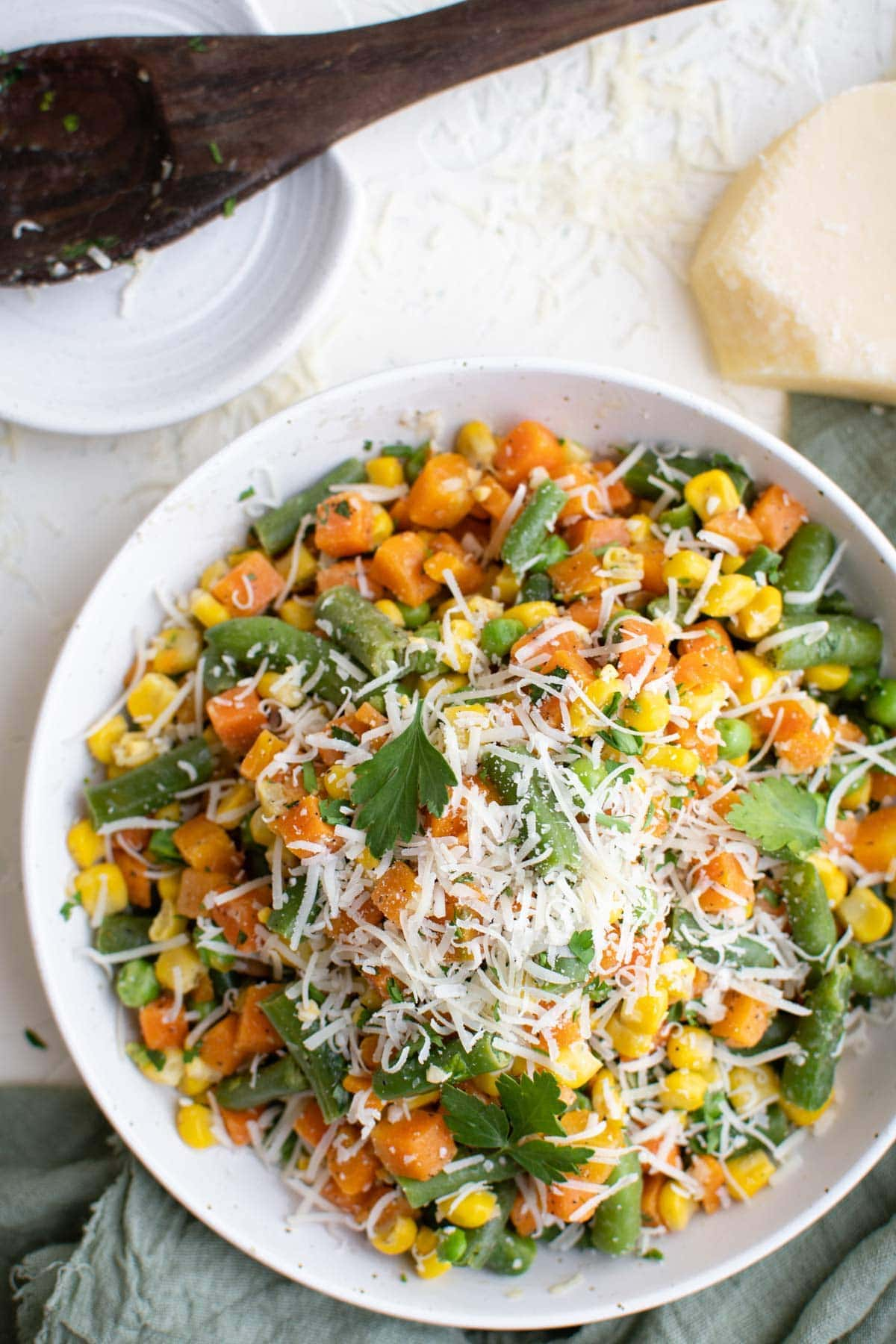 white plate, frozen vegetables, cooked, parmesan cheese, wood spoon