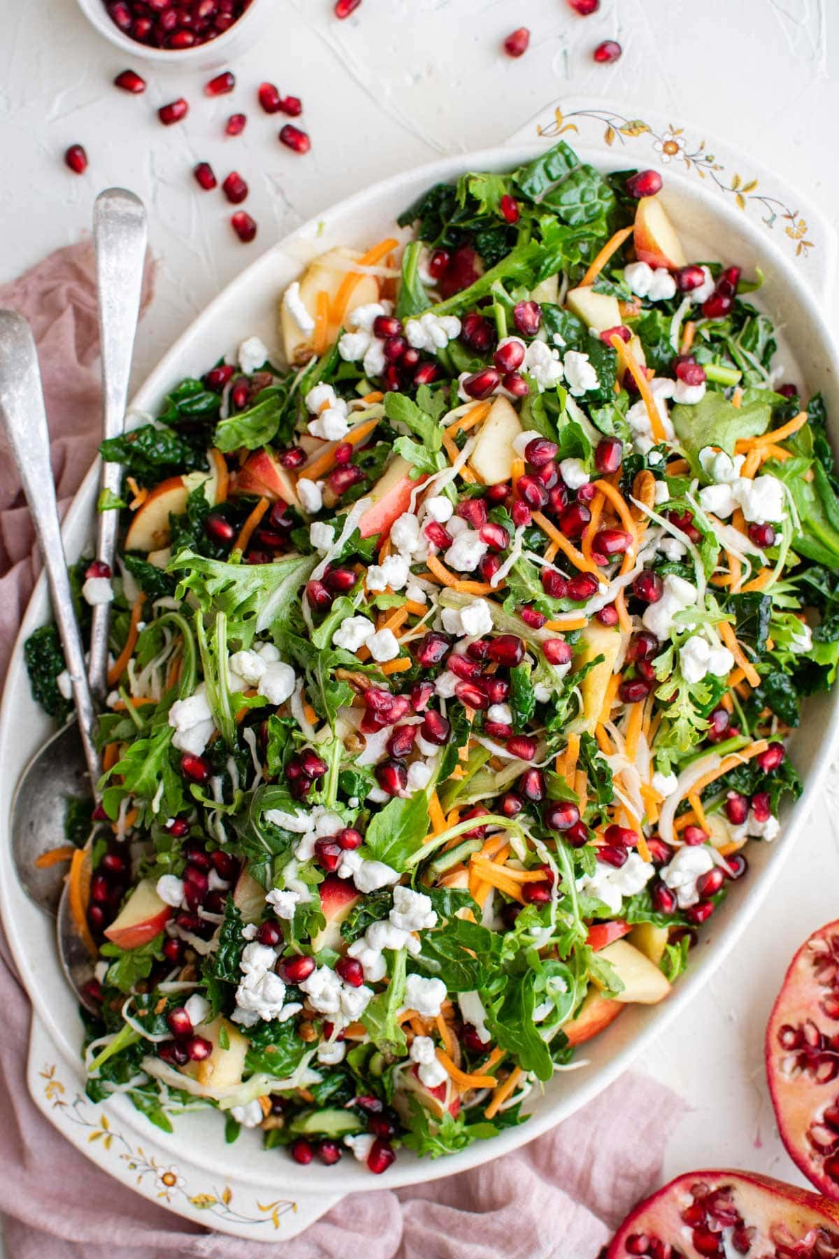 salad with pomegranates, apples, carrots, pecans and goat cheese on a white platter, metal spoons