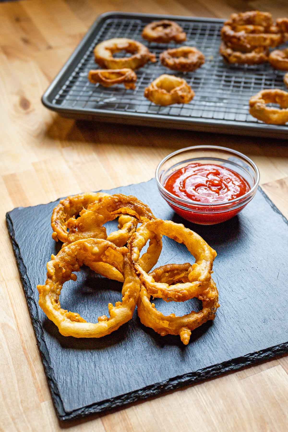 Onion rings and ketchup on table with sheet pan of extra onion rings in background.