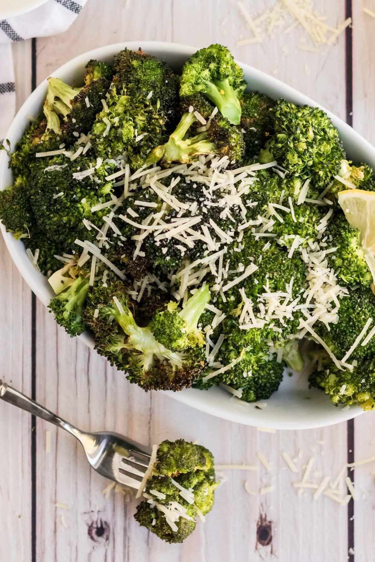 broccoli, white casserole dish, fork, parmesan cheese, lemon