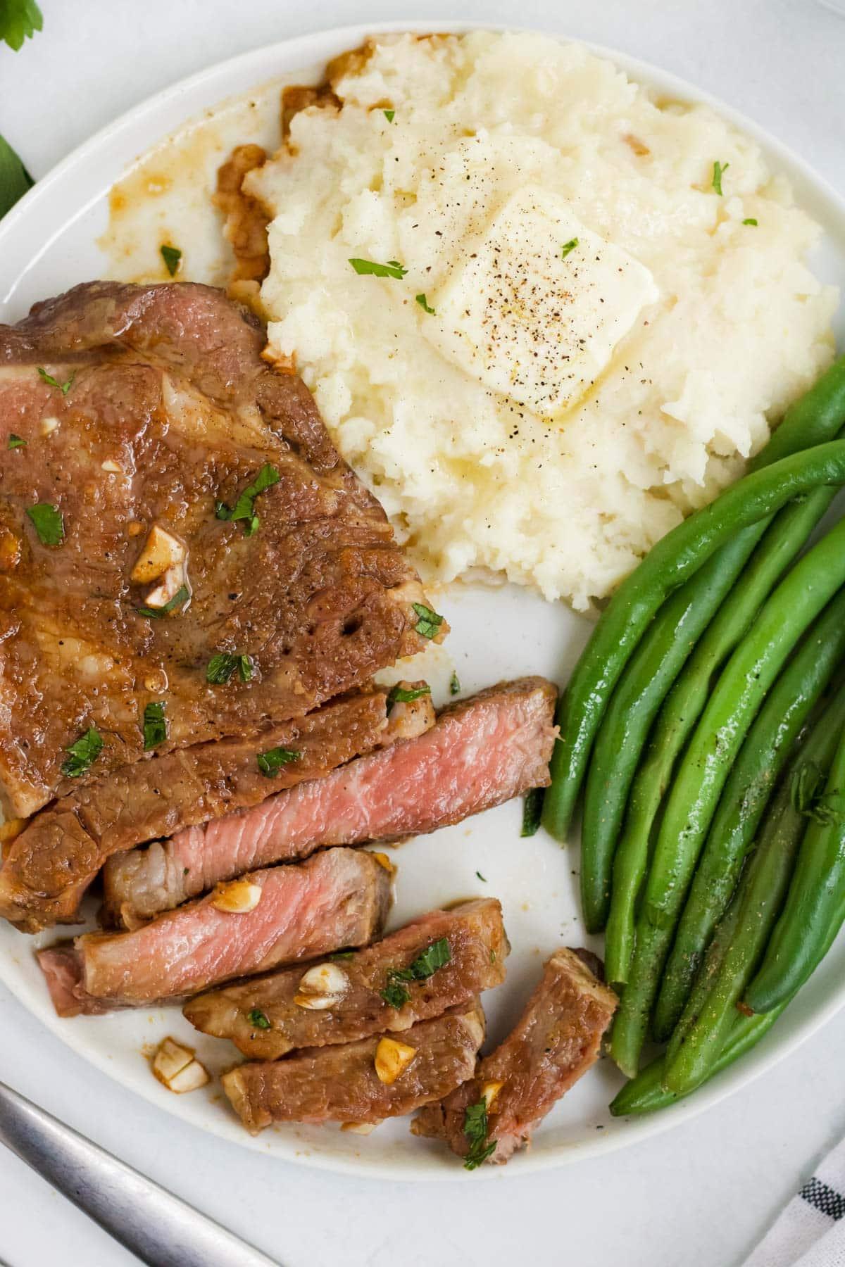 white plate, steak, green beans, mashed potatoes