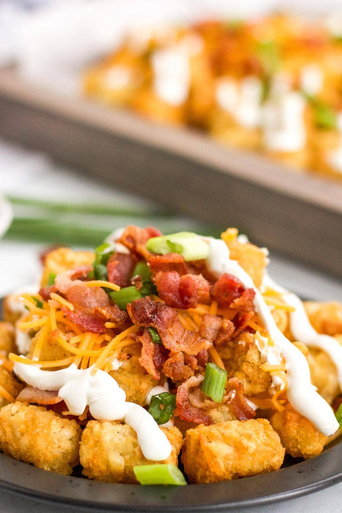 side view of stacked totchos or tater tots with cheese, bacon, sour cream and onions